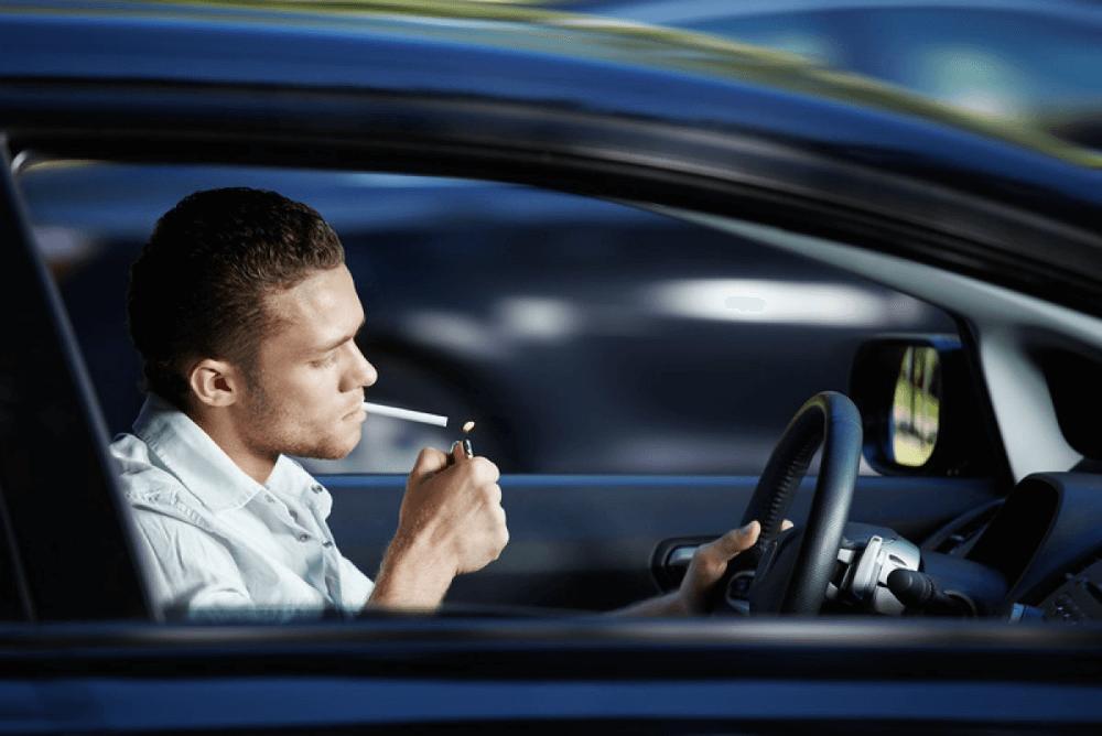 Водитель курит в автомобиле