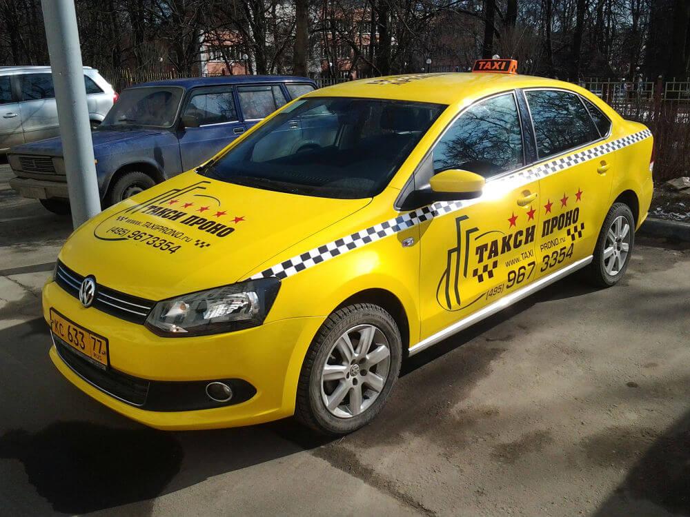 Автомобиль такси с фирменной обклейкой