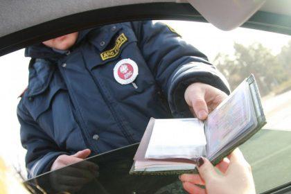 Сотрудник ГИБДД отдает документ водителю