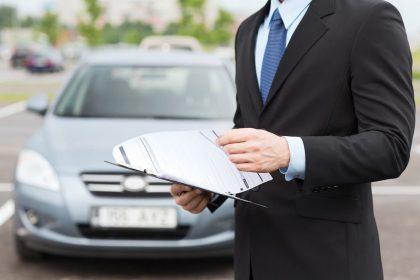 Мужчина в костюме на фоне автомобиля