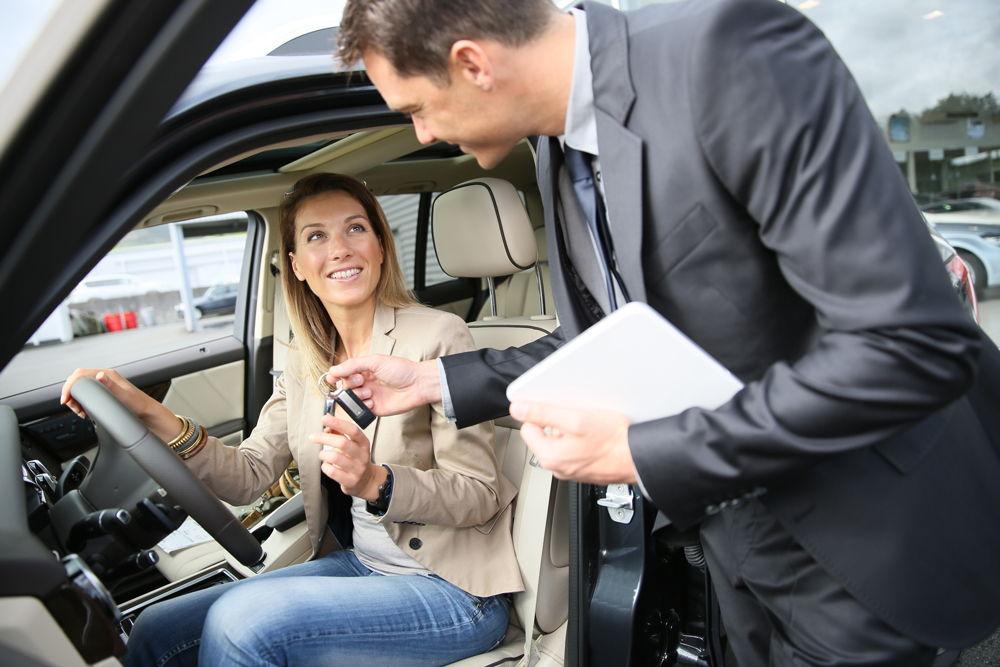Мужчина передает ключи от автомобиля женщине