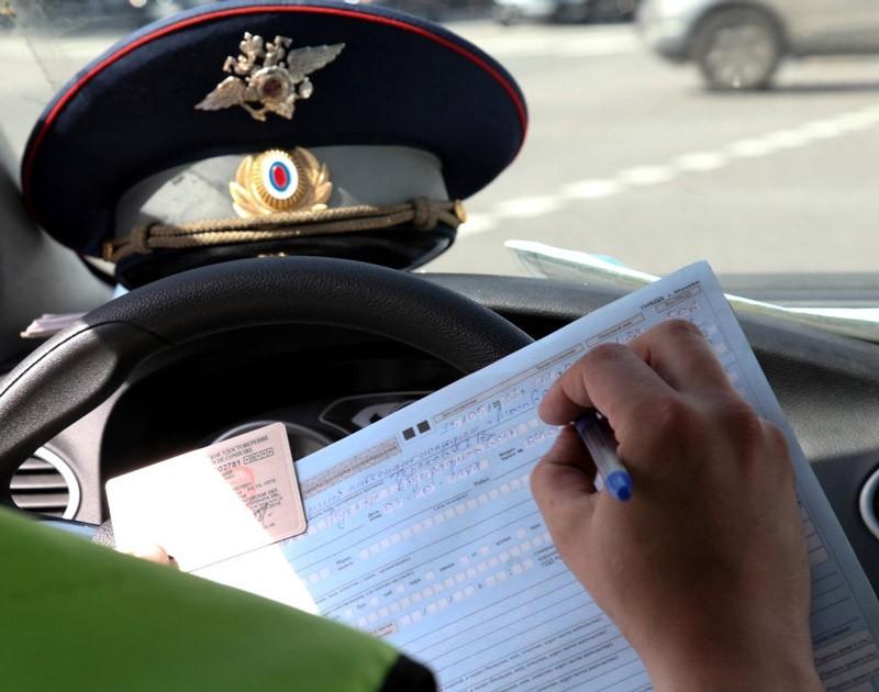 Инспектор ГИБДД выписывает штраф водителю
